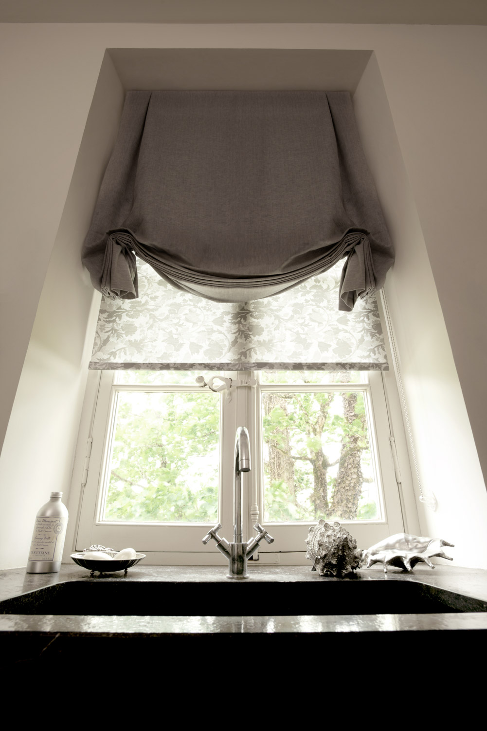 Try a decorative tulip roman shade in a rich fabric. You can even layer it over a light filtering roller shade for extra privacy on your bathroom windows.